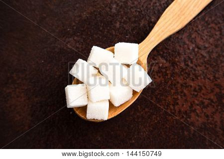 white Sugar cubes on the wooden spoon.