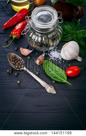 Herbs and spices ingredient for italian food cooking on black wooden board in rustic style