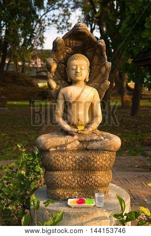 Antique sculpture of a seated Buddha in the morning sun on a city street Chiang Saen. Thailand