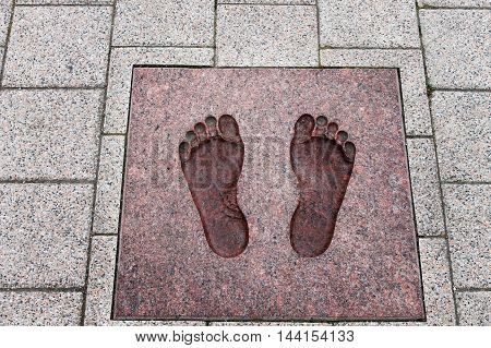 imprint of human footprint on the stone pavement