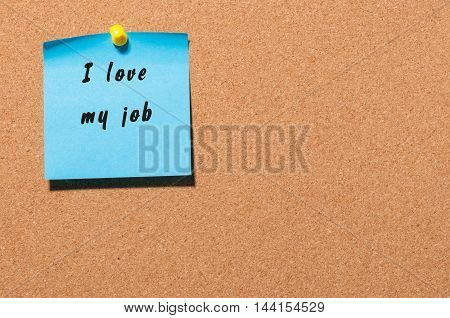 I love my job written on blue adhesive note on notice board background.