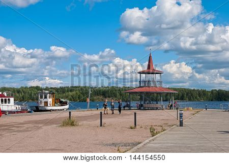 LAPPEENRANTA, FINLAND - AUGUST 8, 2016: Children and adults  near pavilion on the small pier with yachts and boats next to The Saimaa Lake
