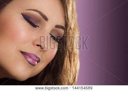 Beauty portrait about woman with closed eyes and purple make up on purple background.
