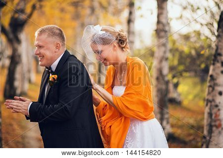 Smiling couple hugging and keeping warm in autumn park. Happy bride and groom in forest, outdoors.