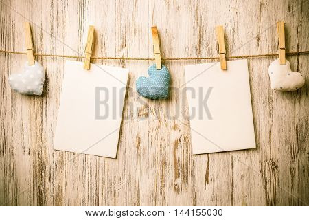 Blank sheet of paper hand made heart pinned to rope on wooden background