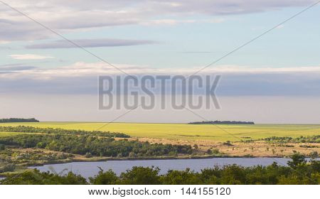 Field of Grass And lake on Blue Sky in morning sun