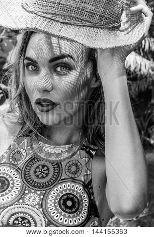 Portrait of beautiful woman in bikini holding straw hat on a sunny day looking into the camera. Black and white photo - face closeup of pretty girl with straw hat pattern shadow on her face
