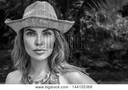 Portrait of beautiful woman with straw hat on a sunny day looking into camera over palm trees background. Black and white photo - eyes closeup of pretty girl with straw hat pattern shadow on her face