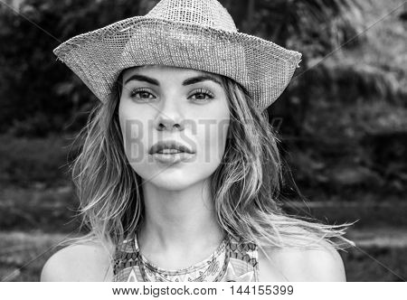 Portrait of beautiful young woman with straw hat on a sunny day looking into camera over palm trees background. Black and white photo - big pretty eyes closeup of attractive girl wearing straw hat