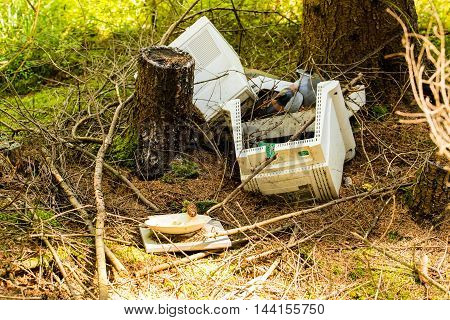 Horizontal photo of old computer which is broken and thrown in the middle of woods between few trees as a sign of non-ecological behavior. Picture represents pollution of environment.