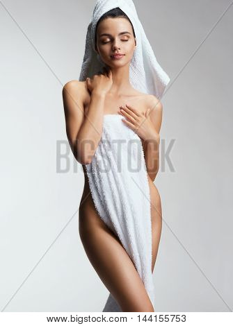 Sensual lady after bath with towel. Photo of young female touching her perfect skin. Youth & Skin care concept