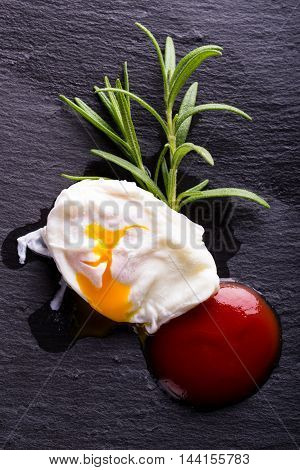 Single Poached Egg On Black Stone With Herb And Ketchup
