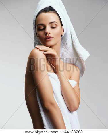 Well-groomed slim girl touching her shoulder. Dressing in pure white towel. Beauty & Skin care concept.