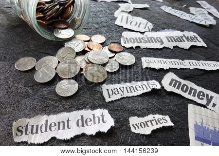 Assorted economy related newspaper headlines with coin jar