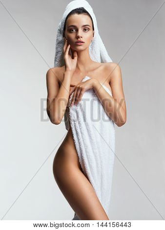Sensual lady posing in white towel. Photo of girl with Perfect slim young body. Youth and Skin care concept