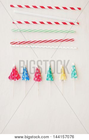 Drinking straws and mixed paper cocktail umbrellas background. Top view, blank space