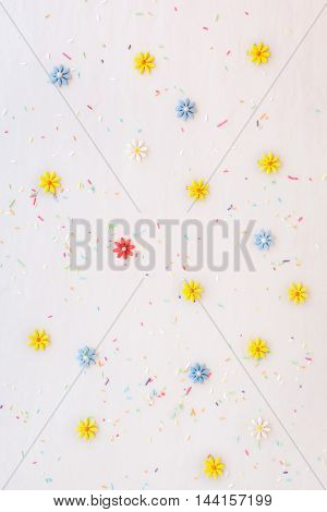Sugar flowers and candy sprinkles scattered on white surface, top view
