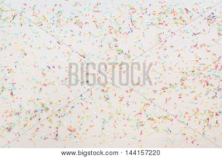 Colorful candy sprinkles scattered on white surface, top view