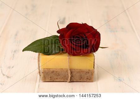 Two bar of soap and a rose on a white background