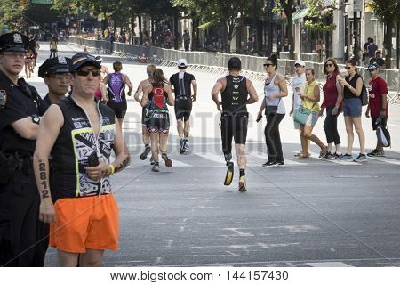NEW YORK -?? JUL 24 2016: ParaTriathlete runs the 10k portion of the NYC Triathlon Race on West 72nd St. The Panasonic New York City Triathlon is the only International Distance triathlon in the city.