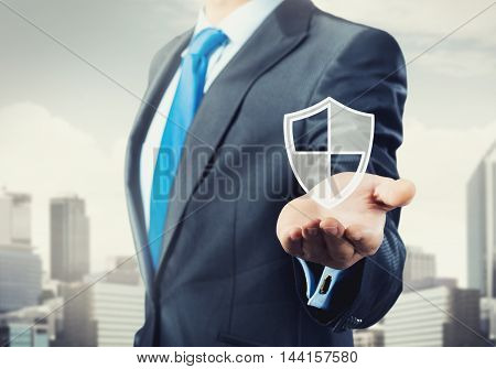 Close view of businessman showing shield icon in palm