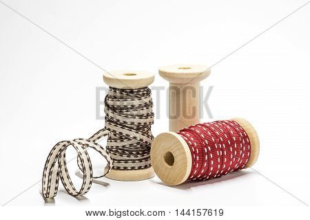 Three wooden spools with ribbons on white