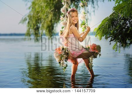 Girl on home made tree swing over river. Swing decorated with flowers. Smiling girl turned around sitting on swing. Girl with flower wreath on head.