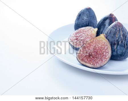 Whole and cut rape figs on the white plate