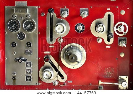 A close up of an olld red finepump gauges