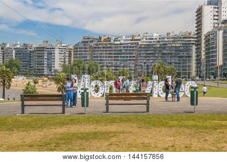 MONTEVIDEO, URUGUAY, DECEMBER - 2015 - Group of tourists at landmark place in which is located the Montevideo letters.