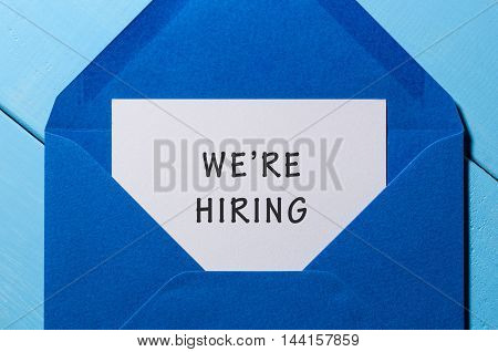 We are hiring phrase written in the paper at blue envelope. human resources concept.