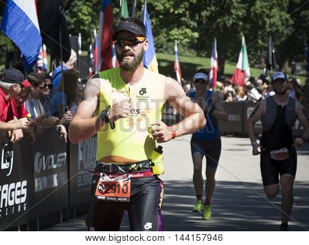 NEW YORK JUL 24 2016: Stefan LeRoy a ParaTriathlete from Achilles International crosses the finish line in Central Park in the NYC Triathlon Race the only International Distance triathlon in the city.