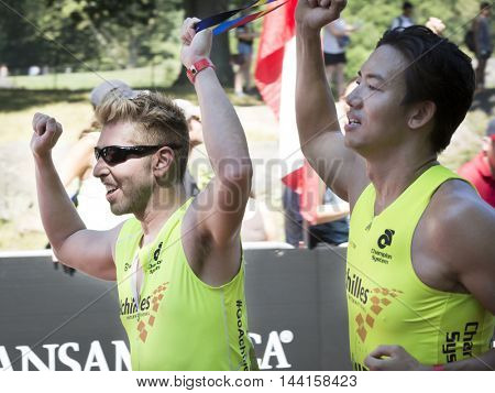 NEW YORK JUL 24 2016: Achilles International athletes cross the finish line of the NYC Triathlon Race in Central Park. The run is 10k and the race is the only International Distance triathlon in NYC.