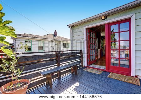 Wooden Deck With A Bench And Red Double Door