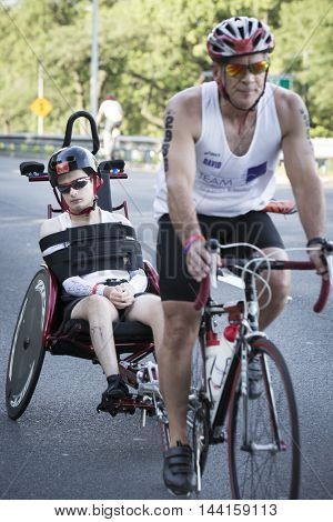 NEW YORK JUL 24 2016: David and Blake Ferrell, a father and son team, compete in the Panasonic NYC Triathlon, biking 40 kilometers mainly on the Henry Hudson Parkway.