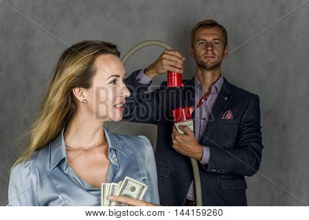 Beautiful girl holding money stares, male cable connects on a gray background