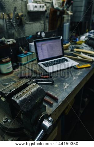 Above view of used hammer, pliers and chisel with laptop and smartphone on metal table