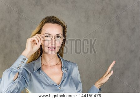 Beautiful girl thoughtfully and attentively looks ahead with glasses on a gray background