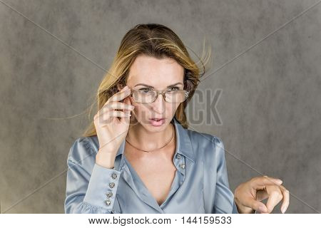 Pretty girl stares forward action on a gray background