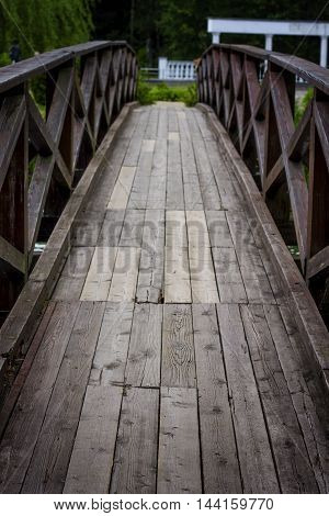 Wooden bridge over the river stretching into perspective