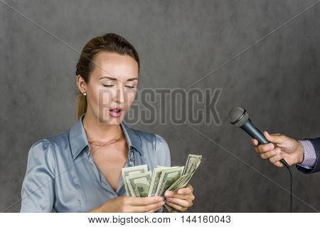 Beautiful girl smiling and looking up and holding in his hand the money over gray background man's hand holding a microphone