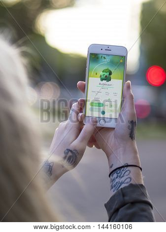 Gothenburg, Sweden - July 26, 2016: Tattooed woman holding a smartphone while playing Pokemon Go, a free-to-play location based augmented reality mobile game developed by Niantic for iOS and Android devices.