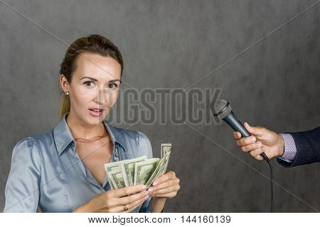 Beautiful girl holding a money man's hand with a microphone interviews on a gray background