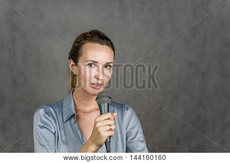 Beautiful girl looking up and holding a microphone on a gray background