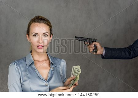 Beautiful girl holding a money and a man's hand with a gun threatens action on a gray background