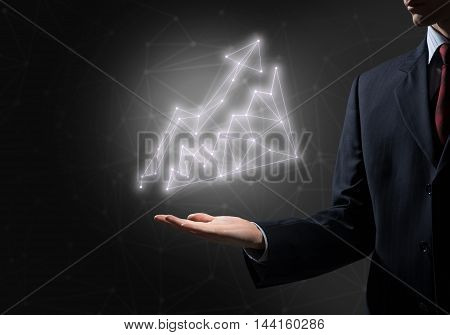 Businessman hand on dark background holding growing graph