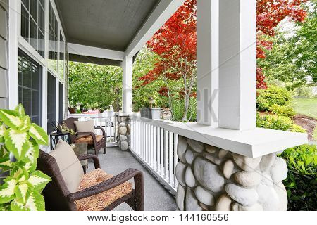 Cozy Entrance Porch With White Columns And Wicker Chairs.