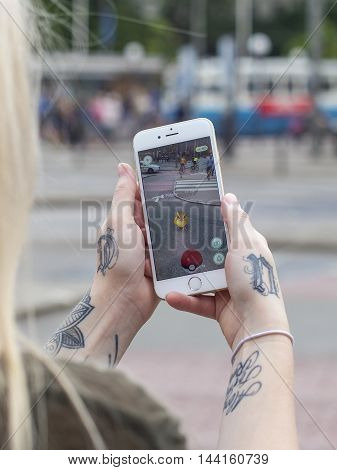Gothenburg, Sweden - July 29, 2016: Tattooed woman holding a smartphone while playing Pokemon Go, a free-to-play location based augmented reality mobile game developed by Niantic for iOS and Android devices.