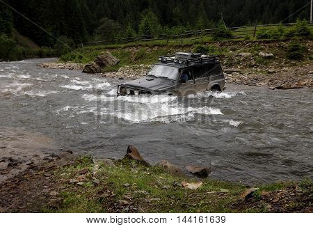 Special off-road vehicle crossing deep mountain river