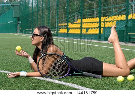 Girl Lies On A Grass Tennis Player With A Racket